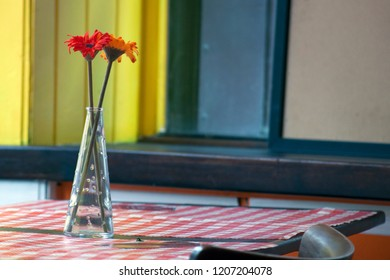 Vases with artificial flowers on the table in the restaurant
