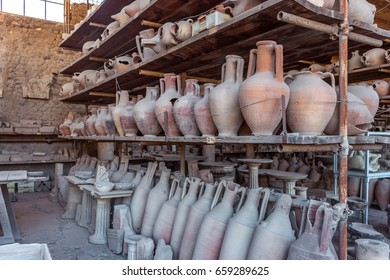 Vases, old amphoras in ruins of Ancient Roman city Pompeii, Campania region, Italy. City destroyed by the eruption of Mount Vesuvius. Ancient dusty pottery from excavations. Bowls with two handles.
