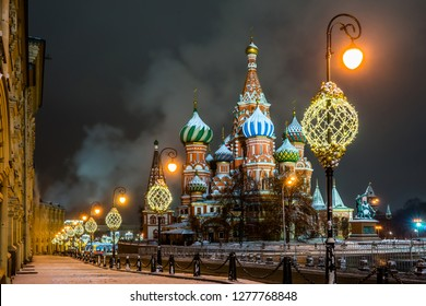 Vasilevsky descent in the winter snowy night. Illuminated Saint Basil`s Cathedral, Kremlin wall and Middle lines on Red Square in Moscow.