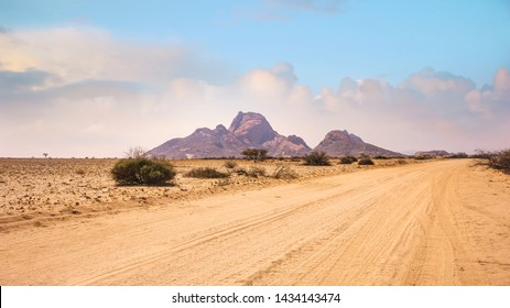 A vast African landscape scene, with a dirt road running through barren flat plains in the Namib Desert toward the huge granite peaks of Spitzkoppe, Namibia.
