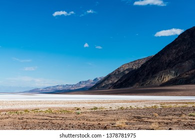 A vast barren desert landscape of salt flats with a mountain range receding into the distance under a blue sky with puffy white clouds - Death Valley National Park