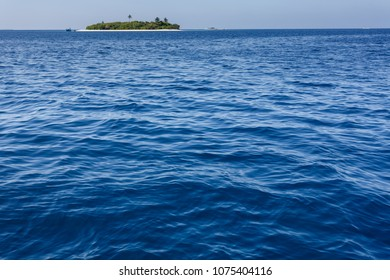 Vast blue ocean and small tropical island in distance