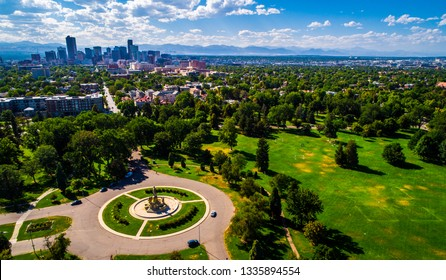 vast City park green spaces circle pattern monument aerial drone view high above Denver , Colorado Downtown skyline in background with Rocky Mountains