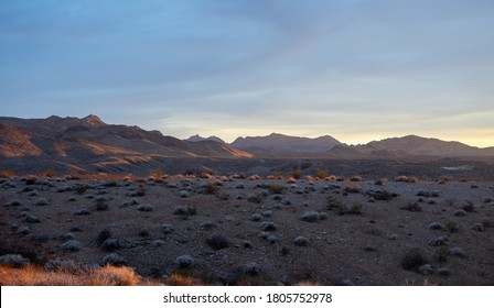 A vast desert terrain with mountains in the background.