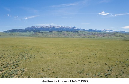 Vast green plains leading to foothills and tall Rocky Mountains.