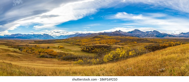 Vast prairie and forest in beautiful autumn. Sunlight passing blue sky and clouds on mountains. Fall color landscape background. Waterton Scenic Spot, Waterton Lakes National Park, Alberta, Canada.