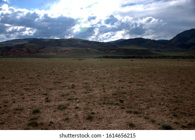 Vast steppe with shallow vegetation at the foot of the hill. Kurai steppe, Altai, Siberia, Russia.
