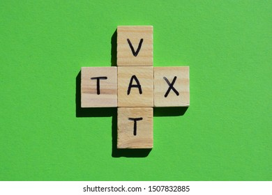 VAT, acronym for Value Added Tax, and Tax in 3d wooden alphabet letters on a bright green background
