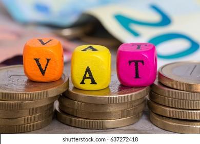VAT letter cubes on coins concept.