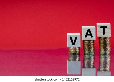 VAT or TAX Concept with wooden block on stacked coins and red background