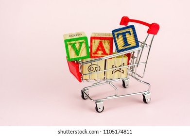 VAT (Value-Added Tax) on household goods concept. Trolley with alphabet (V.A.T) block.