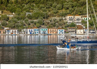 Vathi: July 12th . Greek fishermen entering the harbor and and sailboat exiting. Entrance of Ithaka Vathi in the Ionian Sea. July 12th 2016 Ithaka Vathi, Greece.