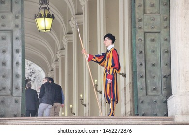Vatican, 10/22/2015 Illustrative Editorial Swiss guardsman with a halberd on the guard of the entrance to the territory, the traditional bright striped costume and weapons.