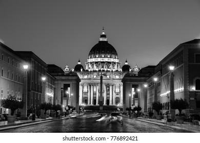 Vatican City. Illuminated St. Peters Basilica in Vatican City at night. Most famous square empty of people in the area, clear blue sky with car traffic lights. Black and white