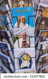 Vatican City, Italy - September 25, 2016: Rack filled with postcards and booklets with photos of Pope Francis' smiling face.