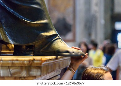 Vatican city, Vatican - October 05, 2018: Person touching the foot of Saint Peter statue. Interior of Saint Peter's Basilica