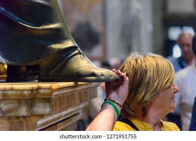 Vatican city, Vatican - October 05, 2018: Person touching the foot of Saint Peter statue. Interior of Saint Peter's Basilica