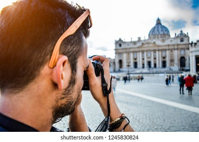 Vatican City, Roma, Italy. Young man taking photo of St Peter's square with the famous Basilica in the background. Concept about architecture, religion, history, people and travel