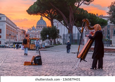 Vatican City, Rome, Italy - April 2, 2019: Street musician lady playing harp near Vatican City in sunset hour, Rome, Italy