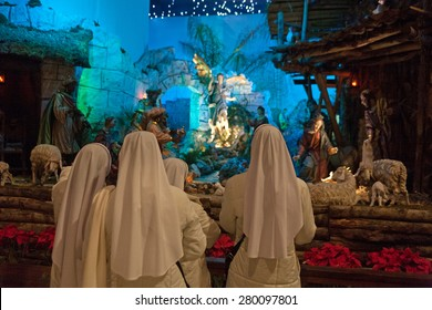 VATICAN CITY, ROME, ITALY - CIRCA JANUARY, 2014 -  A group of nuns staring in front of a nativity scene in Saint Peter's Basilica.