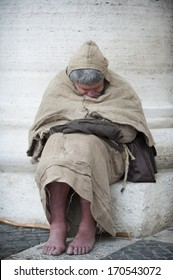 Vatican City, Rome, Italy - March 13, 2013: Man sleeps leaning against to colonnade in St. Peter's Square.