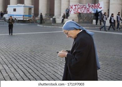 Vatican City, Rome, Italy - March 19, 2013: Sister play with mobile at the hearing of Pope Francis in St. Peter's Square.