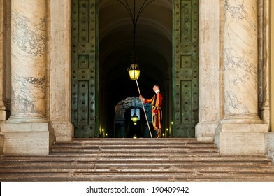 VATICAN CITY - SEPTEMBER 21: unidentified Papal Swiss guard standing at the Vatican Museums door on September 21, 2013 in the Vatican. The Swiss guards served since the late 15th century.