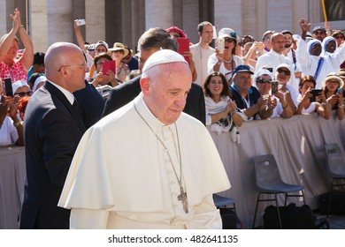 Vatican City - September 3, 2016: Pope Francis is in Piazza San Pietro, is just out of the car and, with a cardinal, walks towards the Basilica. Behind him, a crowd of the faithful cheered.