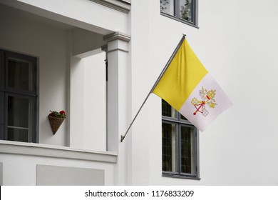Vatican flag. Vatican flag hanging on a pole in front of the house. National flag waving on a home displaying on a pole on a front door of a building. Flag raised at a full staff.