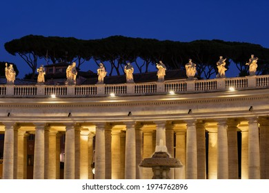 Vatican, monumental colonnade by Bernini illuminated at night on St Peter Square, Doric style columns and statues of saints atop. - Shutterstock ID 1974762896