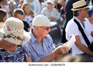 Vatican, Rome, Italy, 09.25.2016. An elderly man reads a booklet, believers in anticipation of the Pope's mass in the Vatican in St. Peter's Square