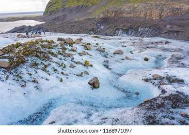 VATNAJOKULL, ICELAND - JULY 29, 2018: Group of tourists taking a guided glacial walk on the amazing Vatnajokull in South Iceland.  Tour includes boots, crampons, safety harnesses, and ice axes.