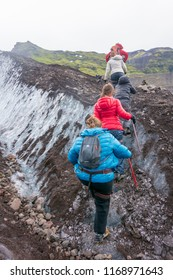 VATNAJOKULL, ICELAND - JULY 29, 2018: Family taking a guided glacial walk on the amazing Vatnajokull glaciar in South Iceland.  Tour includes boots, crampons, safety harnesses, and ice axes.