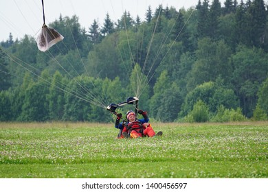 VATULINO, JULY 03, 2018: A tandem of parachute jumpers landing. They are happy and smiling