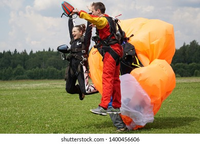 VATULINO, JULY 03, 2018: A tandem of parashute jumpers celebrating the first jump. They are blissful and keeping hands up