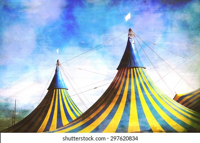 Vaudeville circus tent tops.  Blue and yellow stripes white flag on top.  Vintage effect with blue sky and white clouds above