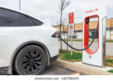 VAUGHAN, CANADA - April 24th, 2019: Close-up of White Tesla Model X charging at Vaughan Mills Tesla Supercharger location.