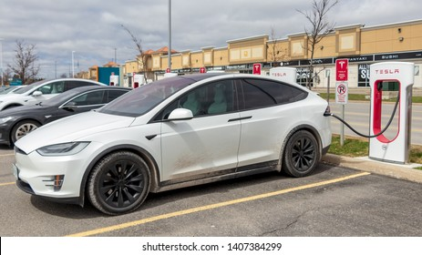 VAUGHAN, CANADA - April 24th, 2019: White Tesla Model X charging with Model S alongside at Vaughan Mills Tesla Supercharger location.