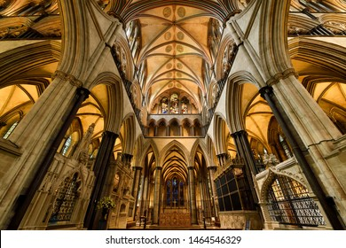 Vaulted ceiling above the front sanctuary and altar of medieval Salisbury Cathedral with stained glass window of Moses in Salisbury, England - June 10, 2019