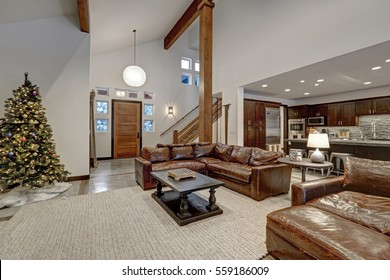 Vaulted ceiling living room accented with wood beams over  brown leather sofas. Open floor plan. Northwest, USA
