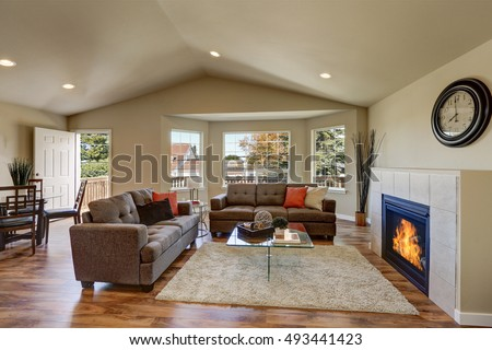 Vaulted Ceiling Living Room With Large Windows, Comfortable Sofas,  Fireplace And Hardwood Floor.