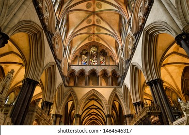 Vaulted ceiling with pillars and arches and stained glass window of Moses above the sanctuary of medieval Salisbury Cathedral Salisbury, England - June 10, 2019