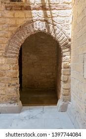 Vaulted open wooden grunge door in bricks stone wall, Old Cairo, Egypt
