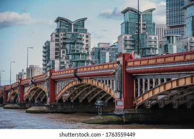 vauxhall bridge panorama with bright sky and clouds and beautiful modern apartment buildings in the background, vauxhall bridge over the thames river in daytime