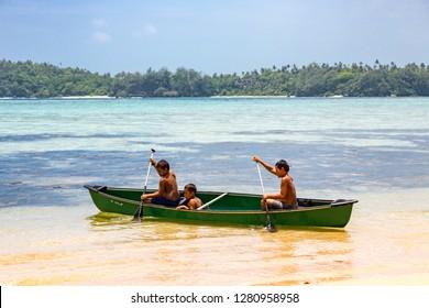 Vavau island, Tonga - Jan 1 2014: Three local native indigenous Polynesian boys rowing in a canoe, Vava'u (Vavaʻu) island, Tonga, Polynesia, Oceania, South Pacific Ocean.