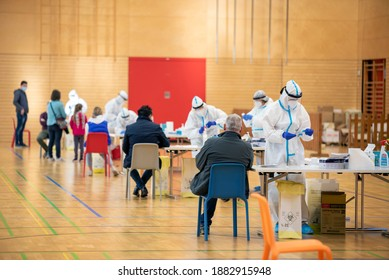 Vax Day: Immunization campaign and mass vaccination. Doctors getting vaccine ready for injection in a public gym. Medical workers giving people Covid-19 antiddote in Milan, on December 27th, 2020.