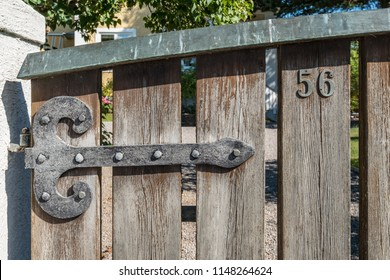 VAXHOLM, SWEDEN - 11 AUGUST, 2018: An iron hinge on a weathered wooden gate to a Scandinavian house displays the number 56.