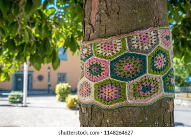 VAXHOLM, SWEDEN - 11 AUGUST, 2018: A tree trunk is wrapped in a crocheted band of multi-colored wool in the square of a Scandinavian town.