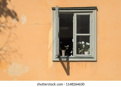 VAXHOLM, SWEDEN - 11 AUGUST, 2018: An open window in the sunlit orange wall of a Scandinavian house displays orchids and geraniums.