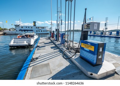 VAXHOLM, SWEDEN - 11 AUGUST, 2018: A motorboat docked at a floating gas station prepares to take on fuel in port on a sunny summer's day.